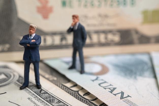 Figura uomo d'affari che sta sul dollaro usa e sulla banconota e sul pensiero di yuan.