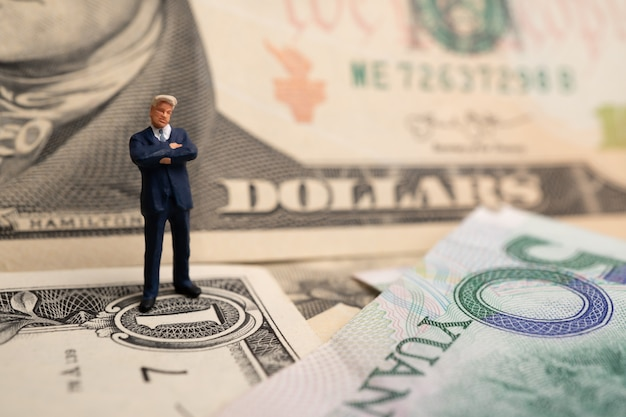 Figura uomo d'affari che sta sul dollaro americano e sulla banconota di yuan