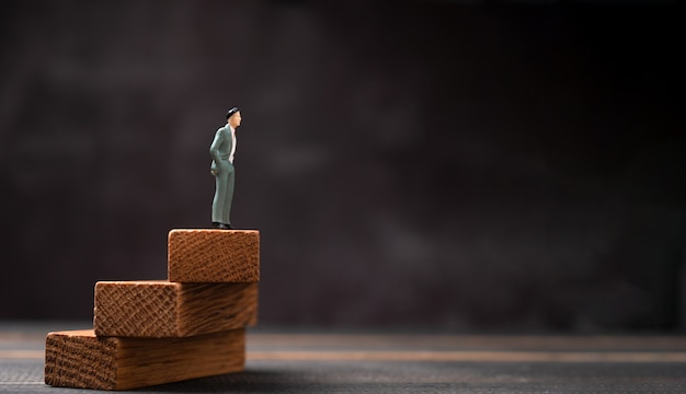 Figura uomo d'affari che sta su un supporto di legno e che guarda al futuro.
