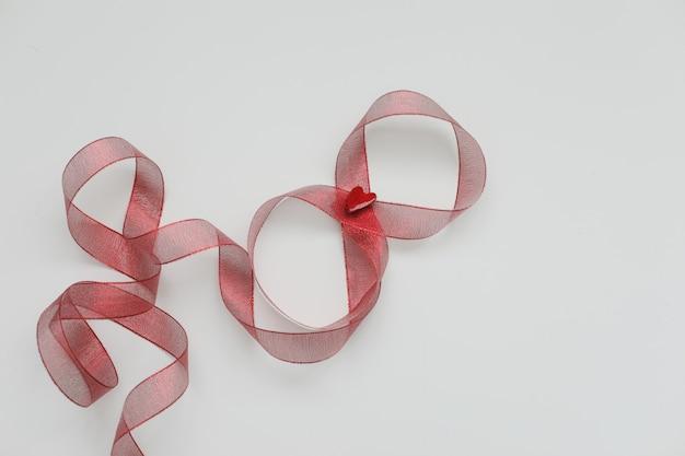 Figura otto del nastro rosso su sfondo bianco.