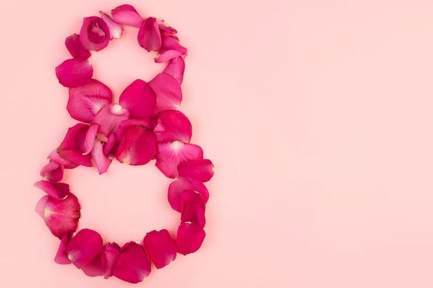 Figura otto di petali di rosa su uno sfondo rosa