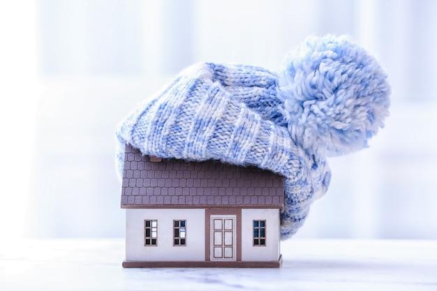 Figura di casa e cappello caldo sul tavolo. concetto di stagione di riscaldamento