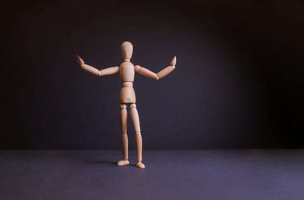 Figura di uomo su sfondo nero gestalt in posa uomo di legno su sfondo nero