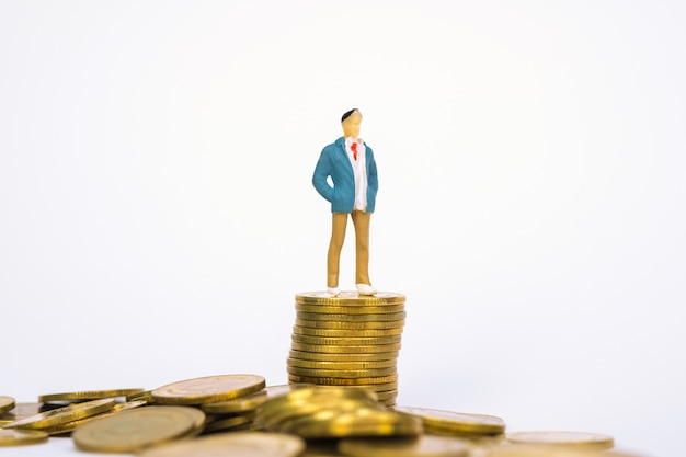 Figura uomo d'affari in miniatura in piedi sulla pila di monete