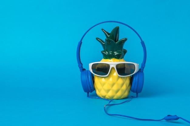 Una figura di un elegante ananas giallo in bicchieri con le cuffie su sfondo blu. l'amore per la musica.