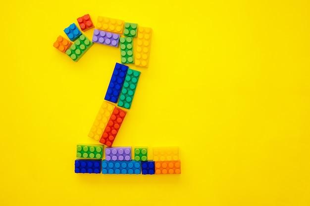Figura due di un costruttore multicolore per bambini su sfondo giallo. spazio vuoto per il testo. secondo posto o due anni.