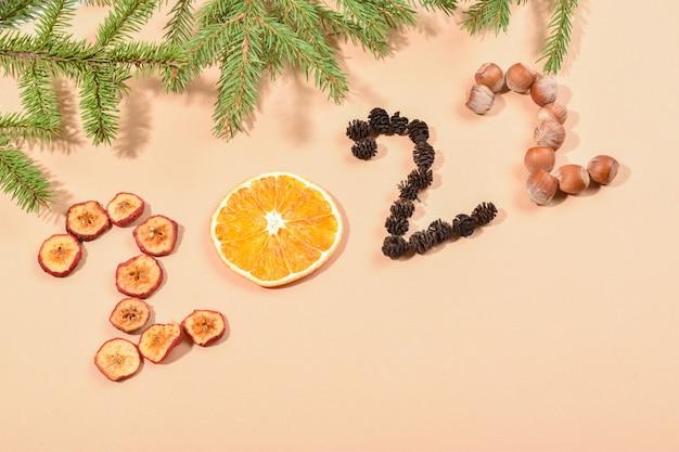 Le figure del nuovo anno 2022 sono realizzate con materiali naturali su fondo beige. felice anno nuovo e buon natale. ecodesign. un luogo da copiare. posizione piatta, vista dall'alto.