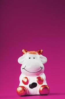 Figurina di una mucca da su uno sfondo rosa, spazio libero per il testo