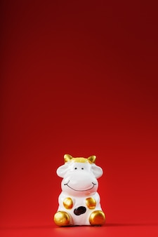 Figurina di una mucca da su uno sfondo rosso, spazio libero per il testo