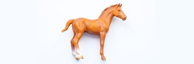 Figurina di un cavallo giocattolo su sfondo bianco. banner