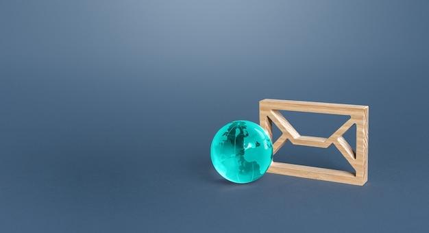 Figurina di una busta di posta e un globo di vetro blu comunicazione attraverso la rete mondiale