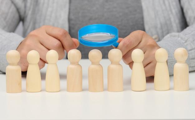 Figurine di uomini su un tavolo bianco, una mano femminile tiene una lente d'ingrandimento su una. concetto di ricerca di dipendenti in azienda, reclutamento di personale, identificazione di personalità di talento e forti