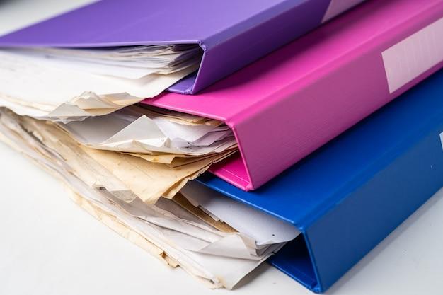 Pila del raccoglitore della cartella di file di multi colore sul tavolo in ufficio