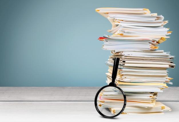 Cartelle di file con documenti e lente di ingrandimento sulla scrivania