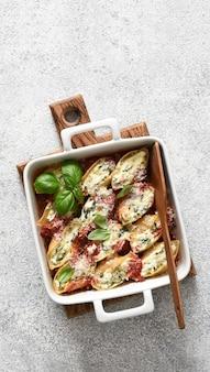 Conciglioni italiani ripieni. conciglioni di ricotta al forno in salsa di pomodoro con parmigiano su una superficie di cemento.pasta al forno con ricotta.