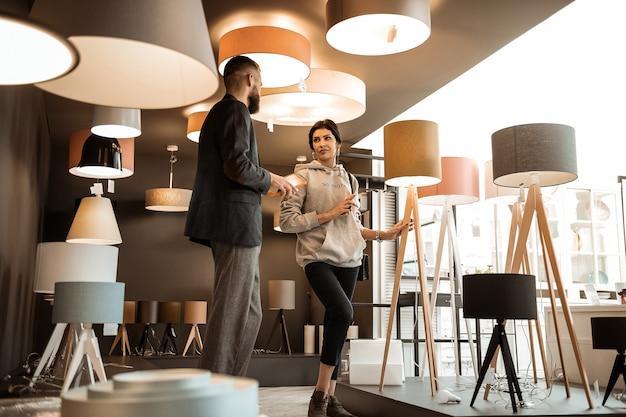 Showroom pieno. coppia attiva in piedi nella stanza piena di apparecchiature per fulmini e conversare con un consulente maschio