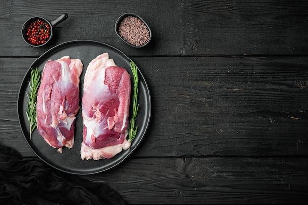 Filetto di anatra cruda, set di carne cruda, sulla piastra, sul tavolo di legno nero