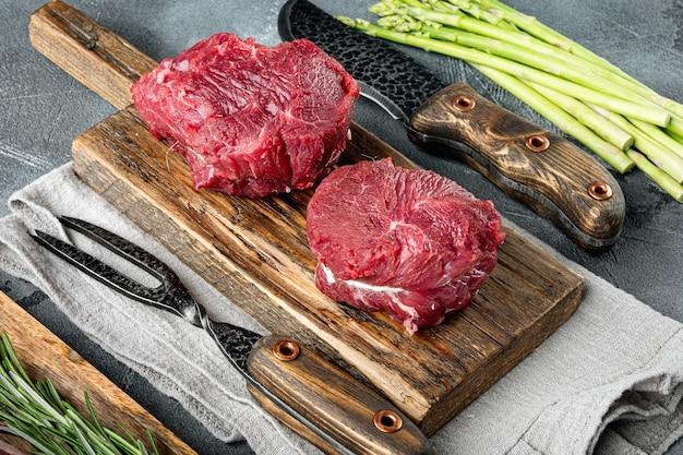 Filetto mignon filetto di carne cruda di vitello e bistecche di manzo, su tagliere di legno, su pietra grigia