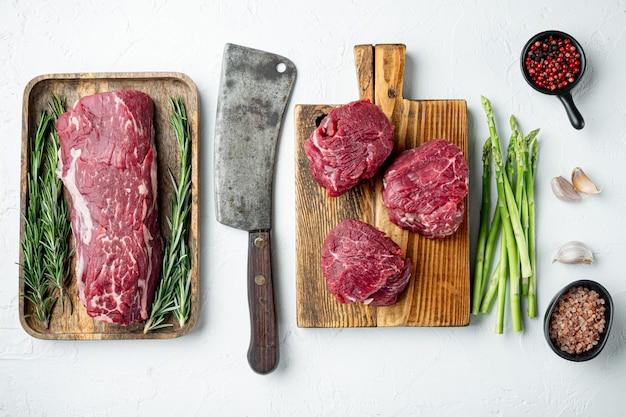 Filetto mignon filetto di carne cruda di vitello e bistecche di manzo, su tagliere di legno, su superficie di pietra bianca