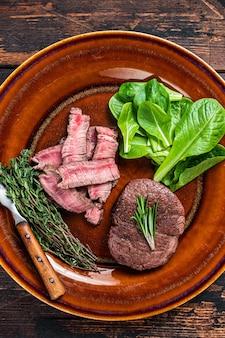 Filetto mignon arrosto di filetto e carne tagliata bistecche di manzo in un piatto con insalata. fondo in legno scuro. vista dall'alto.