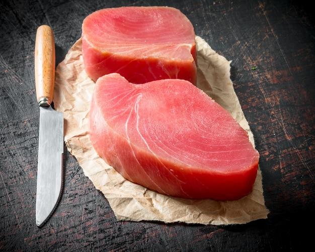 Filetto di tonno crudo sulla carta con un coltello sul tavolo rustico scuro
