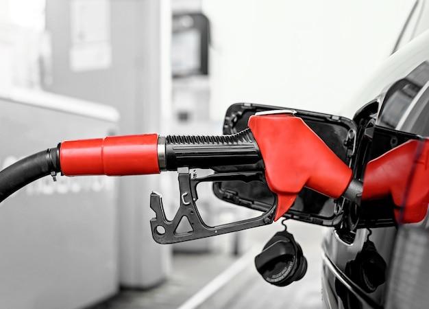 Riempire l'auto di carburante sul primo piano della stazione di servizio. lancia benzina rossa