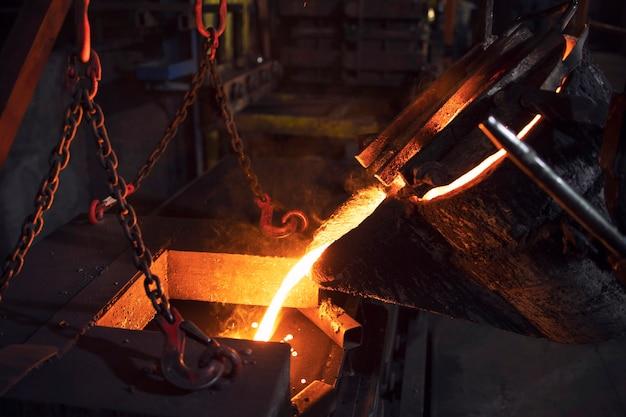 Colata di riempimento con ferro fuso in fonderia per metallurgia e industria.