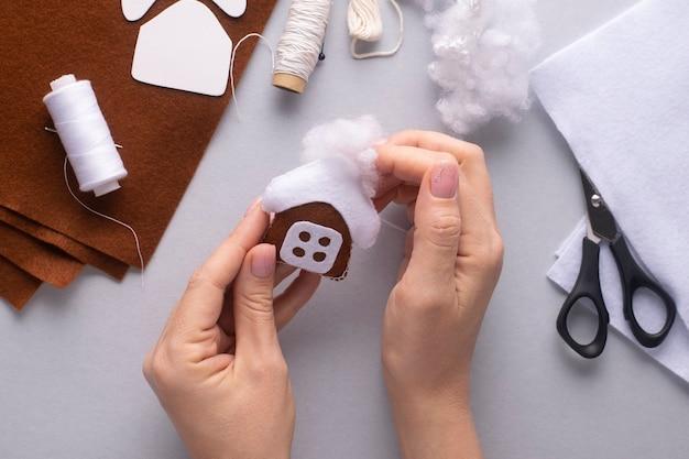 Riempire la casa di panpepato natalizio in feltro con holofiber.