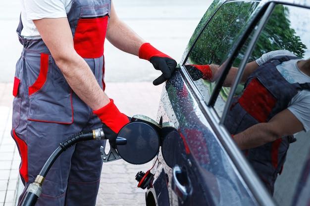 Addetto alla stazione di servizio con un ugello di carburante tra le mani che riempie il serbatoio dell'auto del cliente