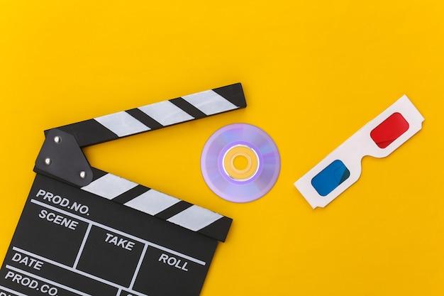 Ciak film, occhiali 3d e cd su sfondo giallo. industria cinematografica, spettacolo. vista dall'alto