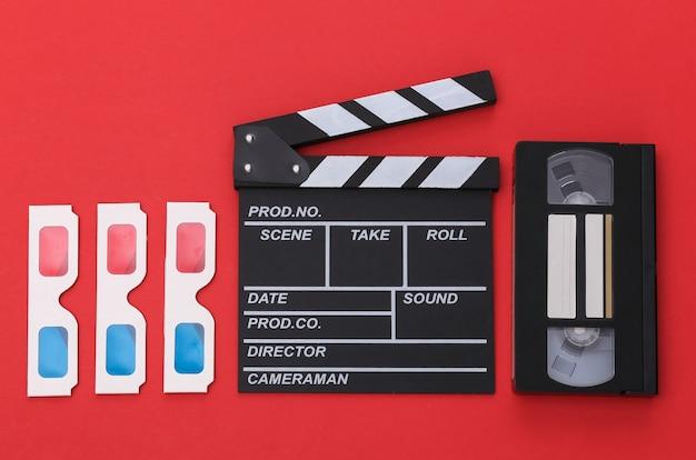Scheda di valvola di film, occhiali 3d, videocassetta su sfondo rosso. vista dall'alto