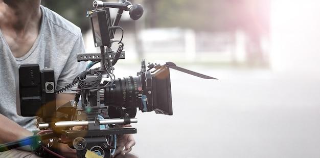 Industria cinematografica riprese con videocamera professionale videografo che tiene in mano una cam 4k su un dslr rig o gimbal
