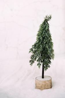 Film rumore verde albero di natale si trova nella neve e uno sfondo bianco. foto verticale minimalista.