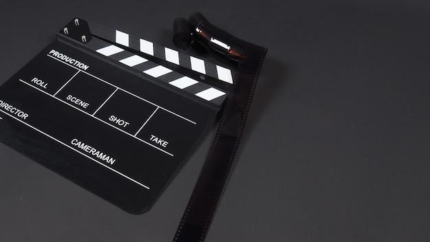 Rotolo di pellicola con ciak o uso di ardesia cinematografica nella produzione video, industria cinematografica su sfondo nero.