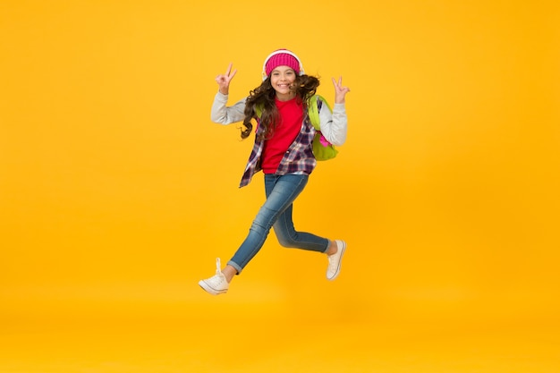 Finalmente vacanza. la bambina ascolta musica in cuffia. piccola studentessa che corre a scuola. affrettarsi. verso la conoscenza della scuola. corri e salta. kid catturato a mezz'aria. felicità e gioia della scuola.
