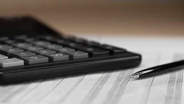 Calcolo finanziario e penna su sfondo marrone