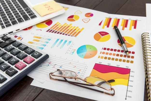 Grafico finanziario con penna per laptop e calcolatrice per analista finanziario, lavoro in ufficio