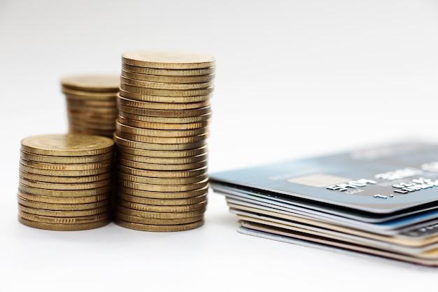 Concetto di finanza, pila di moneta di valuta e carta di credito sulla scrivania.