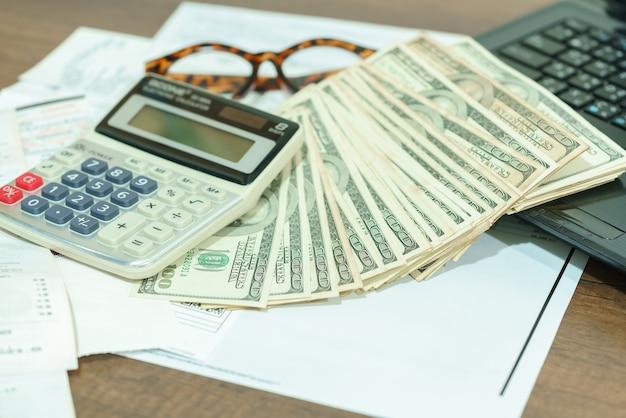 Concetto di finanza: dollaro americano, calcolatrice, fatture, occhiali da vista e computer portatile