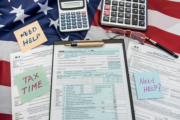 Documento finanziario 1040 modulo fiscale con penna e calcolatrice sulla bandiera degli usa