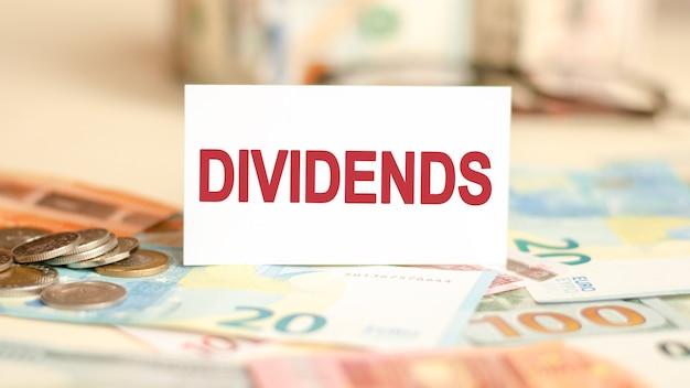 Concetto di finanza ed economia. sul tavolo ci sono banconote, monete e un segno su cui è scritto: dividendi.