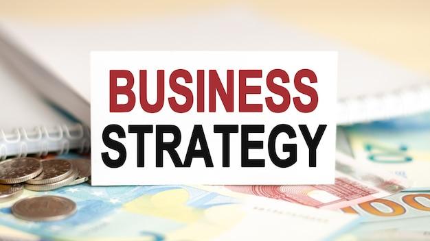 Concetto di finanza ed economia. sul tavolo ci sono banconote, monete e un cartello di carta bianca su cui è scritta la strategia aziendale