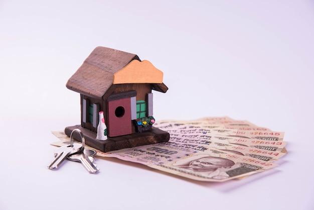 Finanziamento e prestito abitativo o acquisto in india - concetto che mostra il modello di casa 3d, banconote e calcolatrice in valuta indiana ecc