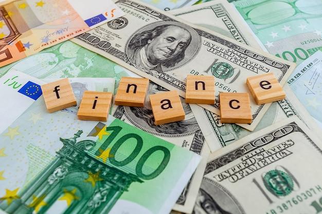 Iscrizione finanziaria su cubi di legno sulla trama di dollari americani e banconote in euro