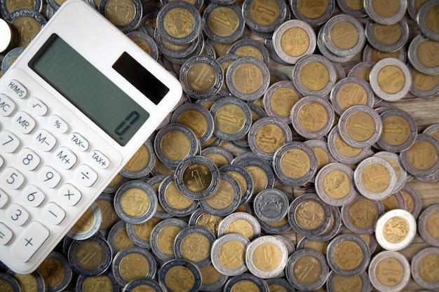 Finanzi le monete messicane in mucchio con il colpo da sopra con il calcolatore a zero