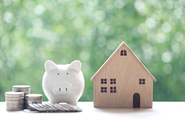 Finanza, casa modello con salvadanaio e pila di monete soldi su sfondo verde naturale, investimento aziendale e concetto di bene immobile