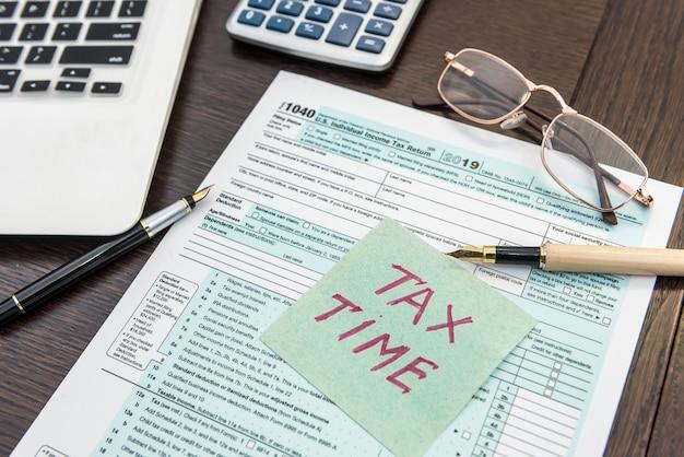 Modulo di imposta finanziaria con calcolatrice, laptop e penna. l'adesivo ha bisogno di aiuto. tempo di contabilità
