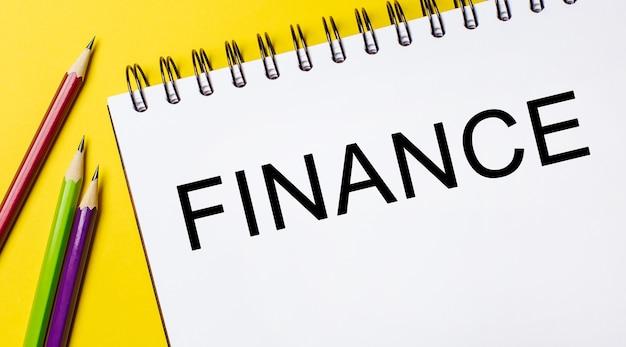 Finanza su un blocco note bianco con matite su sfondo giallo. concetto di affari