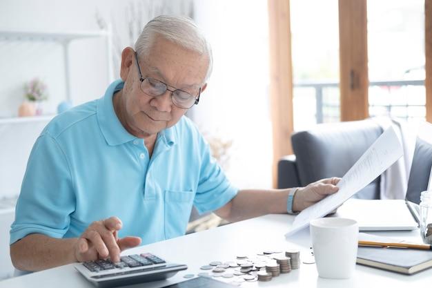Finanze, risparmi, assicurazione di rendita e concetto di persone - uomo anziano con calcolatrice e bollette che contano i soldi a casa. uomo maggiore che calcola le tasse a casa