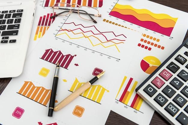 Grafico o rapporto di contabilità finanziaria con penna e calcolatrice in ufficio, economia finanziaria e investimenti